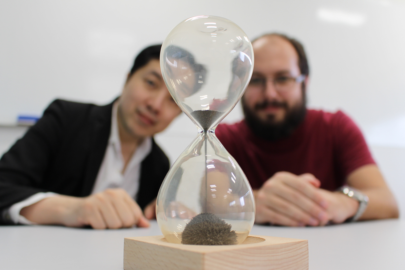Researchers Mile Gu and Thomas Elliott pictured with an hourglass