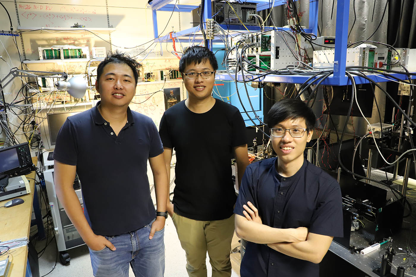 Three researchers in a laboratory at the Centre for Quantum Technologies in Singapore.