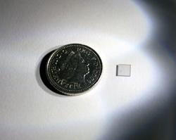 Diamond crystal used in entanglement experiment with a coin for scale